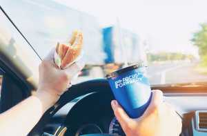 pictured is a driver gripping a burger and soda while driving a moving car
